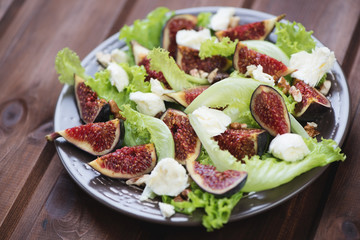 Glass plate with fig fruits, cheese and walnuts salad, close-up