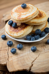 Homemade fritters with fresh blueberries over wooden background