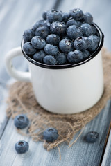 Enameled cup full of freshly picked blueberries covered with dew