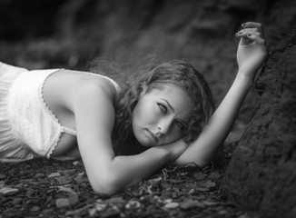 Beautiful woman laid down on the gravel.