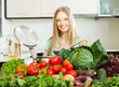 Blonde long-haired woman cooking with  vegetables