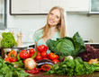 woman with raw  vegetables in home kitchen