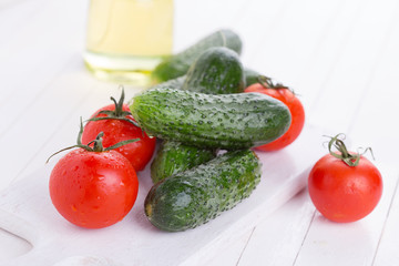 Fresh cucumbers and tomatoes on wooden background