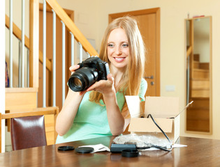 cheerful woman with blond hair unpacking for new digital camera
