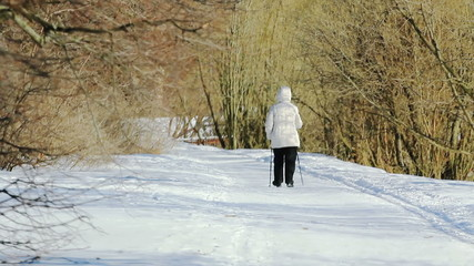 A woman is walking in the park with the help of ski-sticks