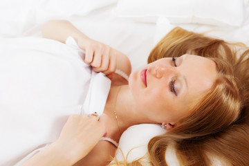 Long-haired woman sleeping on white pillow