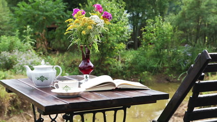 Chaise-longue with a tea table and a book on it, outdoors