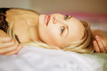 beautiful young woman waking up on the bad, morning light