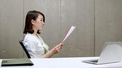 書類を見ながら考えこむ女性