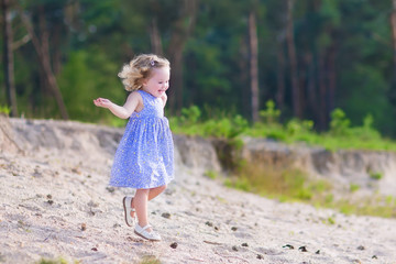 Little girl running in a pine forest