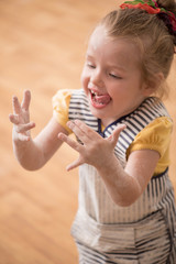 Little cute girl covered with flour laughing