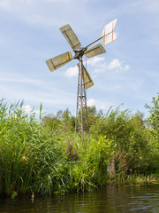 Small and rusted old metal windmill at the waterside