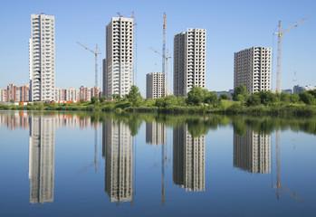 Четыре строящихся здания на берегу озера. Санкт-Петербург