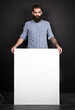 Handsome bearded man holding blank poster.