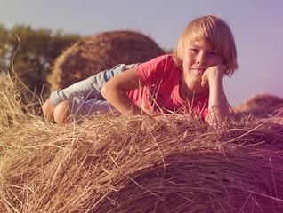Happy little boy sitting on a haystack summer day.