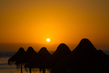 Straw sunshade silhouettes in orange sunset at Tenerife island,