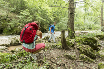 Young woman taking photo of man at hiking