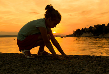 Silhouette of a little girl at the beach