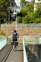 Fahrrad Fahrerin auf Bruecke von hinten