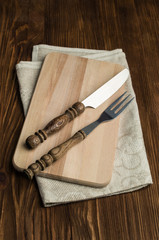 cutlery on a cutting board with linen napkin
