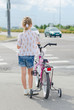 Little girl with bicycle on zebra crossing.