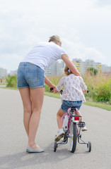Woman teaching little girl to ride a bicycle.