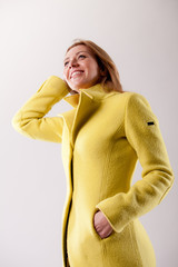 real woman in yellow coat smiling