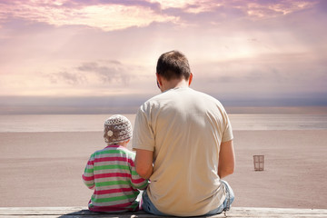 Father and daughter on empty beach at sunset.