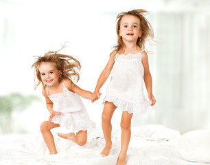 kids twin sisters jumping on the bed, playing and laughing