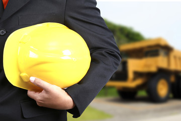 engineer hand holding yellow helmet for workers security against