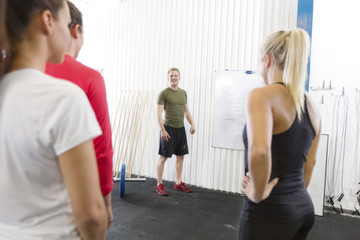 Personal trainer instructs fitness workout team