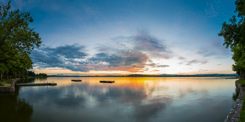 panorama of lake wallersee at sunset with trees and clouds