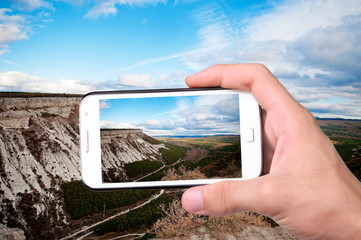 Hands taking photo mountain with smartphone