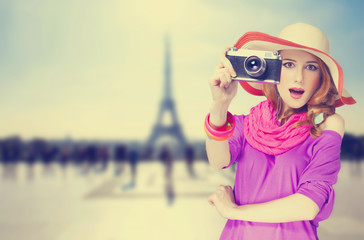 Redhead women with scarf and vintage camera on Parisian backgrou