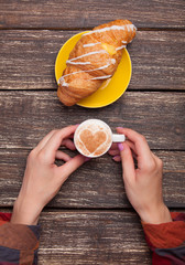 Female hands with cup of coffee and croissant on wooden table.
