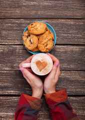 Female hands holding cup of coffee and cookies on wooden table.
