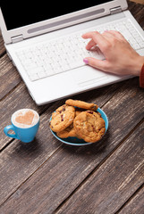 Cookie and women hand with notebook.
