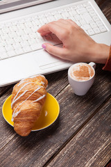 Croissant and women hand over laptop.
