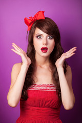 Surprised girl in red dress on violet background.