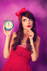 Surprised girl with alarm clock on violet background.