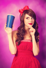 Brunette girl with bottle on violet background.