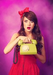 Beautiful brunette girl with telephone on violet background.