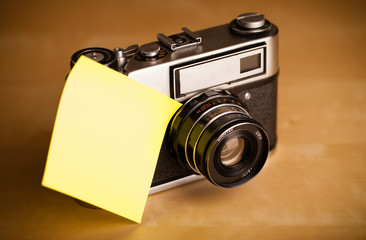 Empty post-it note sticked on photo camera