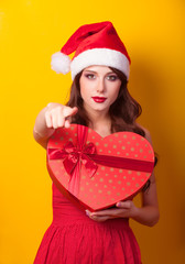 Beautiful brunette girl in christmas hat with gift on yellow bac
