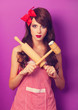 Beautiful brunette housewife with rolling pin on violet backgrou