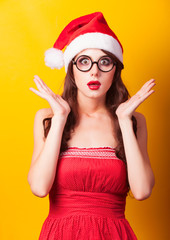 Beautiful brunette girl in christmas hat with glasses on yellow