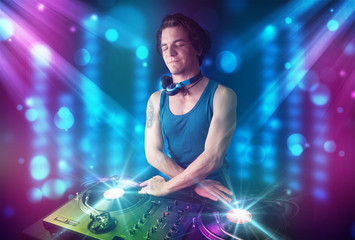 Dj mixing music in a club with blue and purple lights