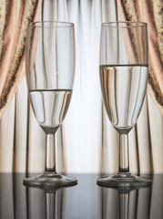 two glasses of champagne with curtains in the background