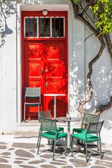 Street cafe terrace in front of a red door in Mykonos