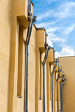 Drainpipes on yellow wall poster